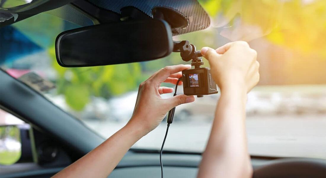 На фото водитель настраивает прикрепленный к лобовому стеклу автомобильный видеорегистратор