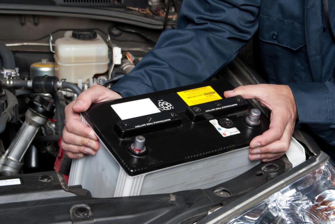 На фото автомастер виймає автомобільний акумулятор з машини для того щоб його зарядити