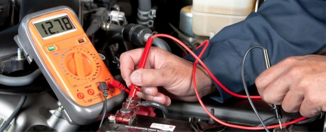 На фото автомастер перевіряє заряд автомобільного акумулятора за допомогою мультиметра, на дисплеї якого показано 12.78 вольт