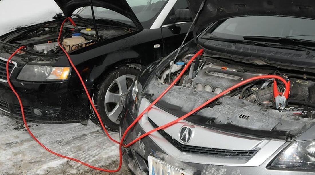 На фото взимку проводиться зарядка акумулятора одного автомобіля від акумулятора іншого авто. Дві машини стоять поруч