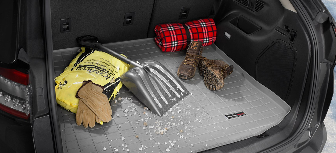 На фото коврик в багажник, на нем различные вещи - лопата, перчатки, ботинки. Коврик в багажник защищает багажный отсек