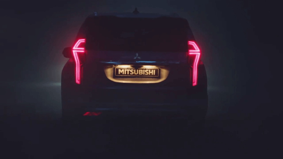 На фото Мицубиси Паджеро. Автомобиль едет ночью. Задние сигналы стоп горят красным цветом.