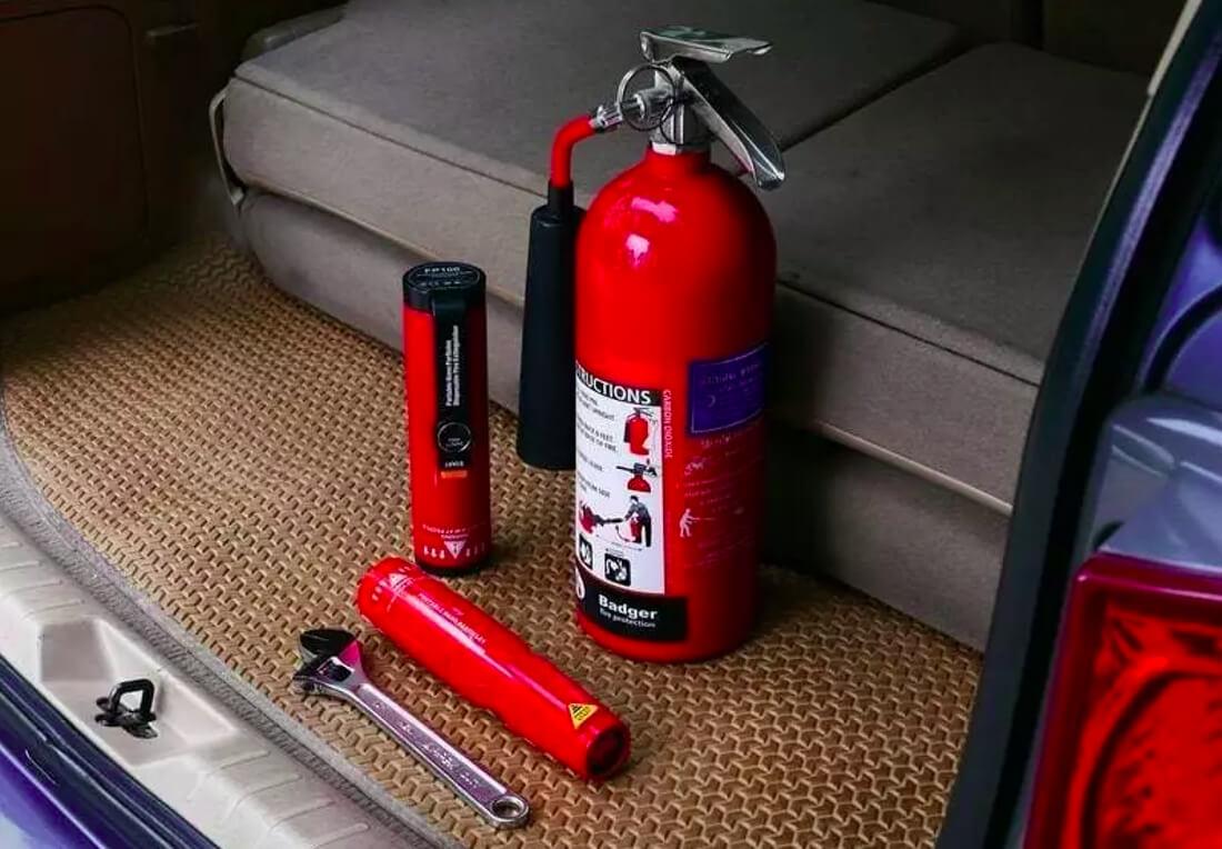 На фото в открытом багажнике автомобиля стоит огнетушитель и два аэрозольных баллона красного цвета