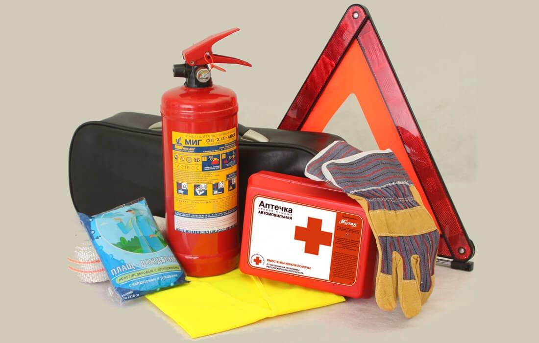 На фото стандартный набор автомобилиста, который состоит из аварийного знака, огнетушителя, аптечки, троса, рукавиц и чехла