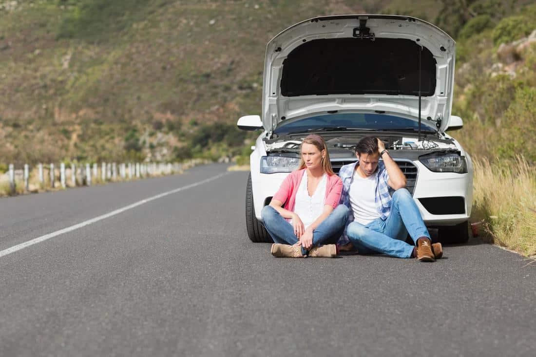 На фото перед заглохшим автомобилем белого цвета с открытым капотом на асфальте сидят грустный водитель и его спутница