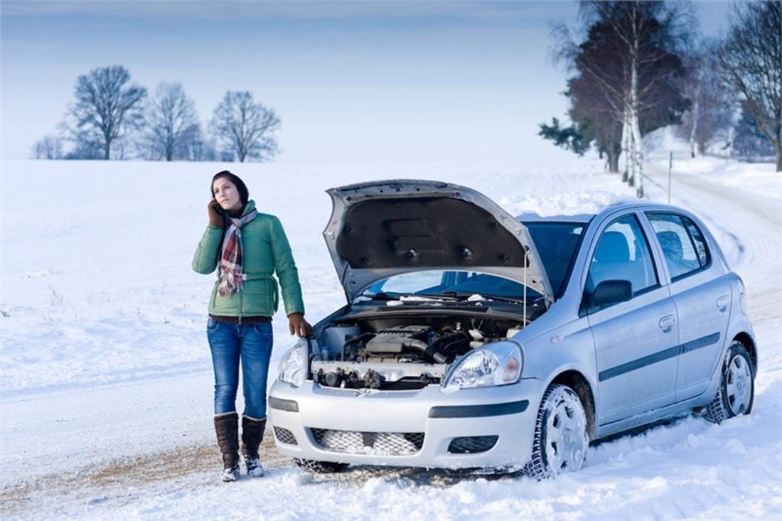 На фото женщина-водитель зимой стоит возле открытого капота захлохшего автомобиля серебристого цвета, вызывает помощь по телефону