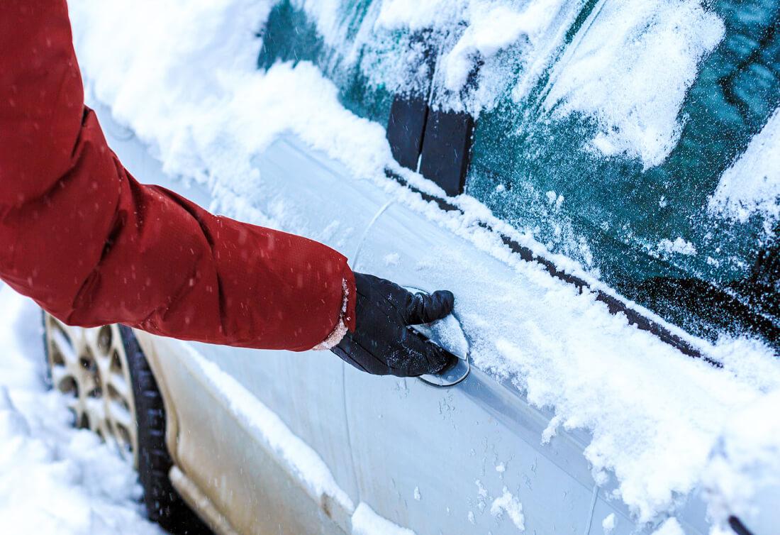 На фото водитель пытается открыть примерзшие двери машины, предварительно очистив автомобиль от снега
