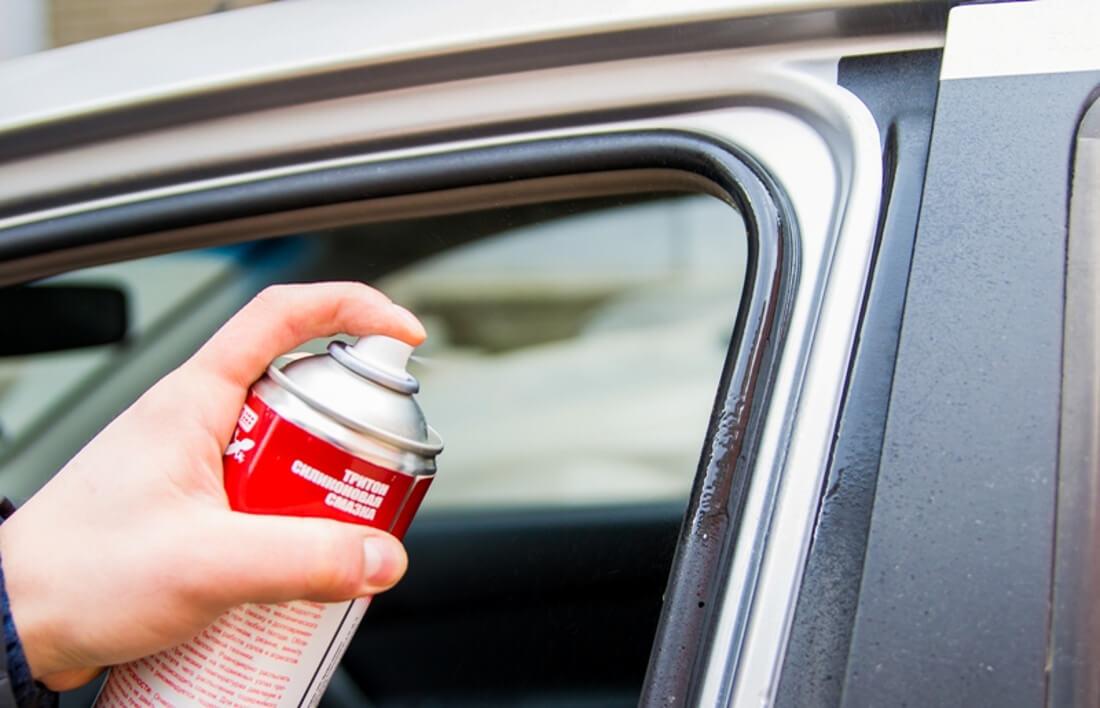 На фото водитель использует силиконовую смазку на уплотнитель автомобильной двери, чтобы избежать примерзания двери зимой