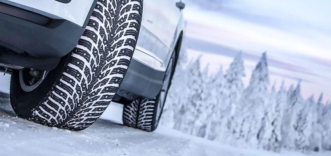 На фото белый автомобиль зимой в заснеженной местности. На переднем плане зимняя шипованая резина