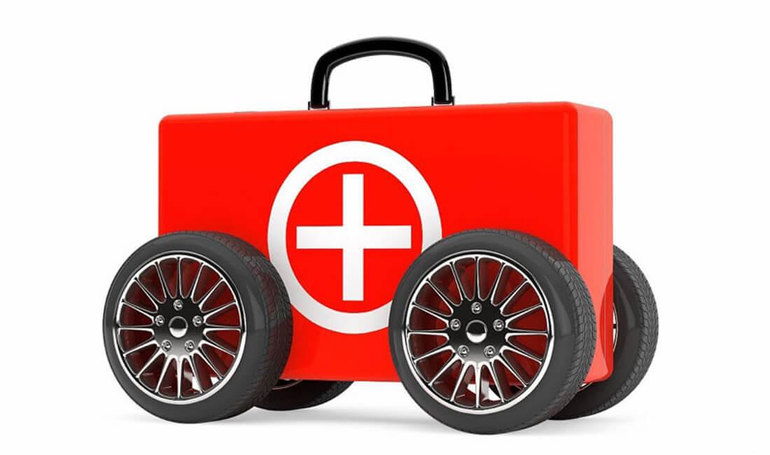 На фото автомобильная аптечка красного цвета с колесами от автомобиля