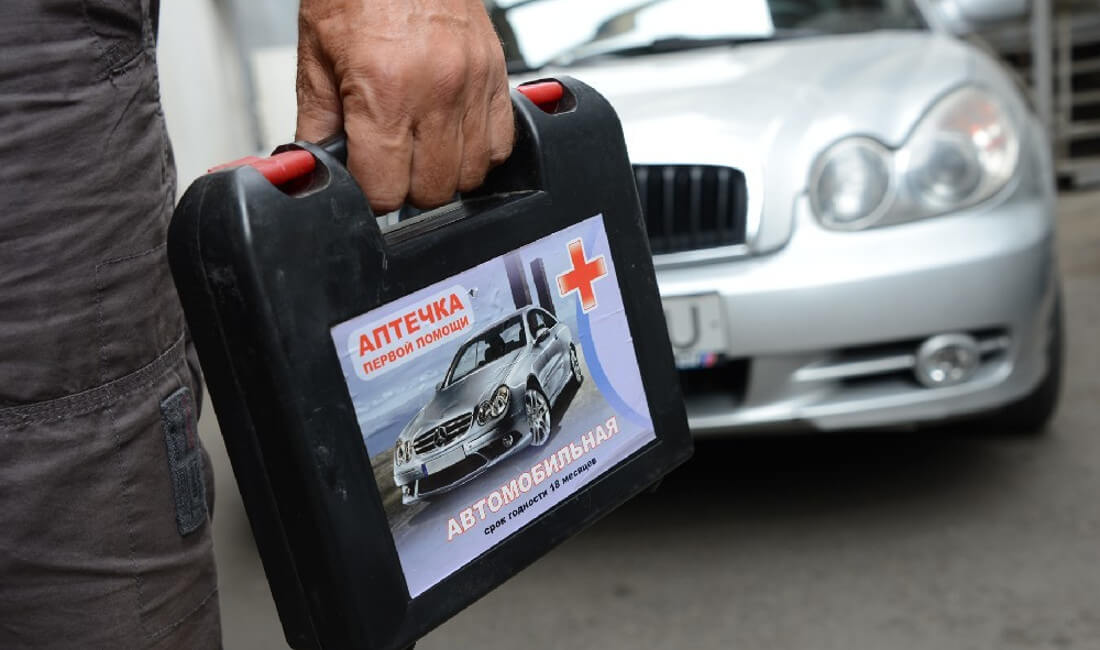 На фото автомобильная аптечка в руке водителя. Н заднем фоне автомобиль