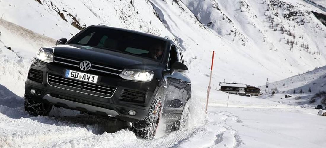 На фото автомобиль в заснеженной горной местности с цепями на колесах пробирается по снежной дороге