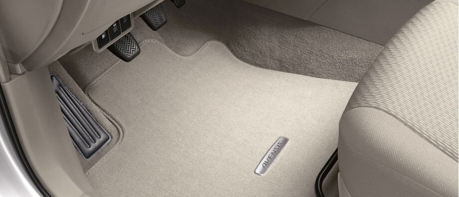 на фотографии ворсовый коврик в салон автомобиля, он светло серого цвета и расположен рядом с водительским сиденьем