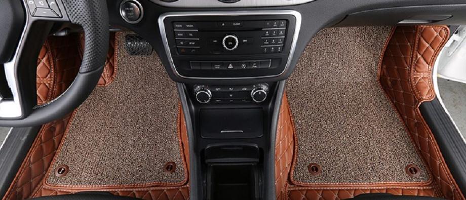 на фотографии два ворсовых коврика серо коричневого цвета, они расположены возле сиденья водителя и пассажира
