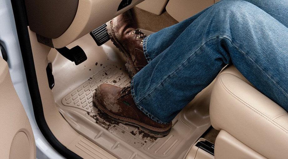 На фото водитель в очень грязных ботинках в салоне автомобиля. Грязь повсюду. Чтобы салон был чистым, необходимо купить резиновый коврик в авто